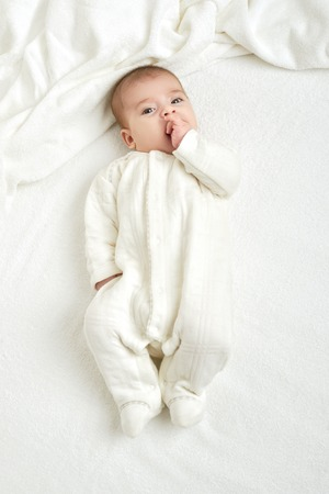 baby portait lie on white towel in bed, yellow toned