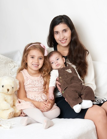 Mother with her children sit in the bed with teddy bear, happy family portrait Stock Photo