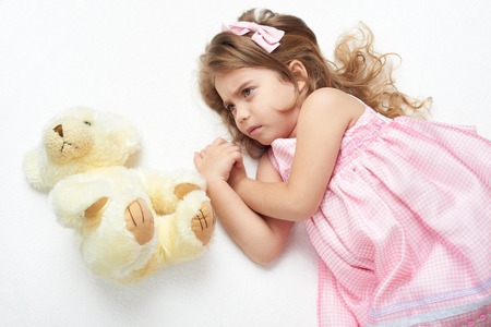 angry teddy: angry girl child with teddy bear lie on white towel in bed, dressed in pink