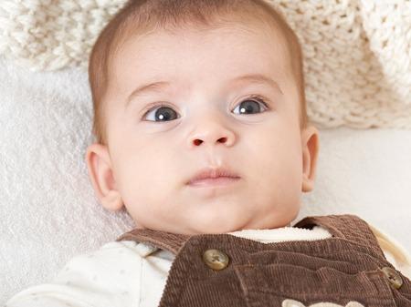 bebé mentira retrato en una toalla blanca en la cama, en tonos amarillo