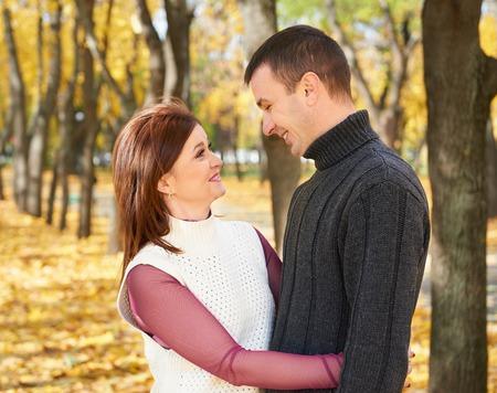 feliz pareja de adultos abrazo en el parque de la ciudad del otoño, los árboles con hojas amarillas, sol brillante y emociones feliz, la ternura y los sentimientos