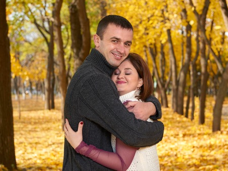 gente romántica, adulta feliz abrazo de los pares en el parque de la ciudad del otoño, los árboles con hojas amarillas, sol brillante y emociones feliz, la ternura y los sentimientos