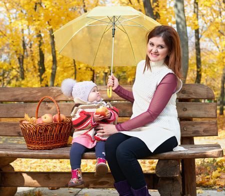 apples basket: Woman with child girl in autumn city park sit on bench with apples basket and umbrella and having fun, happy family Stock Photo
