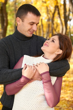 feelings and emotions: romantic people, happy adult couple embrace in autumn city park, trees with yellow leaves, bright sun and happy emotions, tenderness and feelings Stock Photo