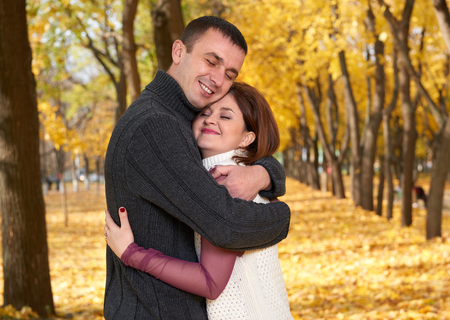 tenderness: romantic people, happy adult couple embrace in autumn city park, trees with yellow leaves, bright sun and happy emotions, tenderness and feelings Stock Photo