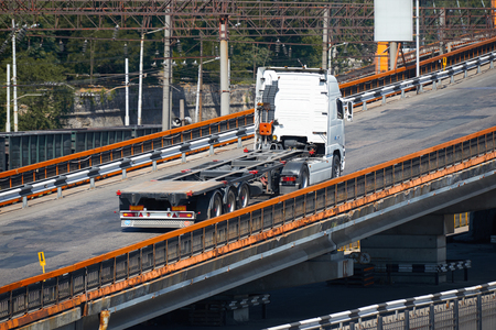 lading: empty truck on road, rides up over the bridge, industrial infrastructure and railroad in sea port, cargo transportation, delivery and shipping concept