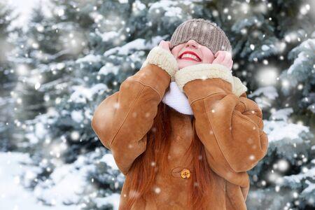 beautiful woman on winter outdoor, snowy fir trees in forest, long red hair, wearing a sheepskin coat