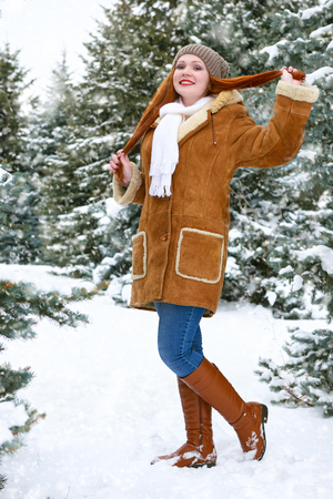 beautiful woman full length on winter outdoor, snowy fir trees in forest, long red hair, wearing a sheepskin coat Stock Photo