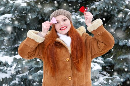 beautiful woman on winter outdoor posing with heart shape toys, holiday concept, snowy fir trees in forest, long red hair, wearing a sheepskin coat Stock Photo