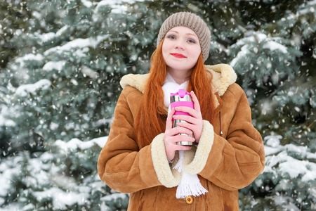 beautiful woman drinking a hot drink and keep warm on winter outdoor, snowy fir trees in forest, long red hair, wearing a sheepskin coat Stock Photo