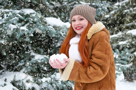 glades: beautiful woman play with snow on winter outdoor, snowy fir trees in forest, long red hair, wearing a sheepskin coat Stock Photo