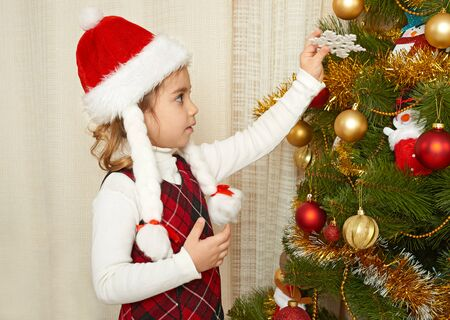 happy girl portrait in christmas decoration, winter holiday concept, decorated fir tree and gifts