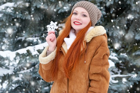beautiful woman on winter outdoor posing with big snowflake toys, holiday concept, snowy fir trees in forest, long red hair, wearing a sheepskin coat Stock Photo