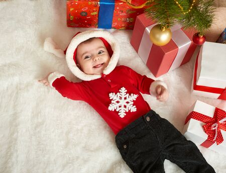 baby near christmas tree: happy baby portrait in christmas decoration, lie on fur near fir tree and gifts, winter holiday concept