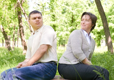 spat: Unhappy couple in summer park. Face expression and grimace.