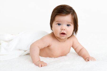 Baby lie on white towel. Child in bed. Stock Photo