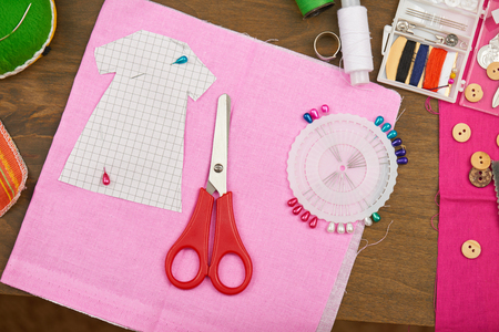 the pattern of clothing, sewing accessories top view, seamstress workplace, many object for needlework, embroidery, handmade and handicraft Stock Photo
