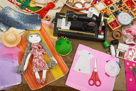 handmade doll and clothing pattern, sewing accessories top view, seamstress workplace, many object for needlework, embroidery and handicraft