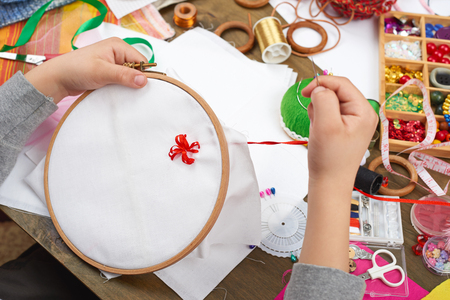 messy clothes: boy embroidered on the hoop, hand closeup and red ribbon on white textile, learns to sew, job training, handmade and handicraft concept Stock Photo