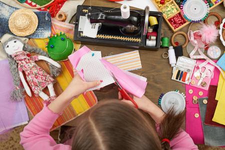 Meisje naait poppenkleding, bovenaanzicht, naaien accessoires bovenaanzicht, naaisterwerk werkplek, veel object voor naaldwerk, handgemaakt en ambachtelijk