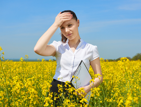 Sad business woman in flower field outdoor with clipboard touch head. Young girl in yellow rapeseed field. Beautiful spring landscape, bright sunny day