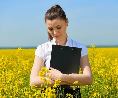 Sad business woman in flower field outdoor with clipboard. Young girl in yellow rapeseed field. Beautiful spring landscape, bright sunny day Stock Photo