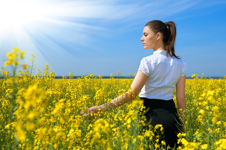 Girl in yellow flower field with sun, beautiful spring landscape, bright sunny day, rapeseed