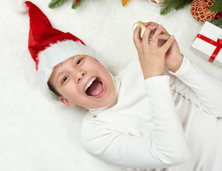 boy child having fun with christmas decoration, face expression and happy emotions, dressed in santa hat, lie on white fur background, winter holiday concept Stock Photo