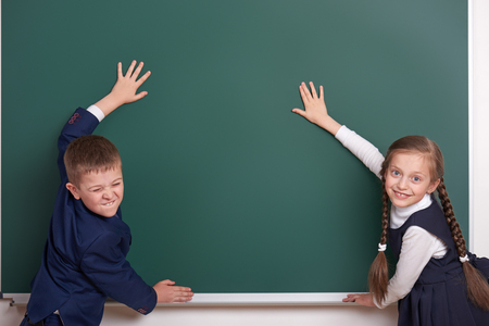 study group: elementary school boy and girl put hands on chalkboard background and show blank space, dressed in classic black suit, group pupil, education concept