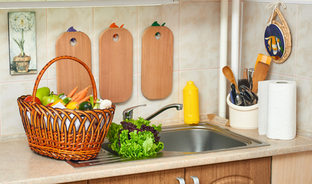 vegetables and fresh greens in basket in kitchen interior, healthy food concept