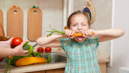 boca cerrada: child girl eat carrot, vegetables and fresh fruits in kitchen interior, healthy food concept