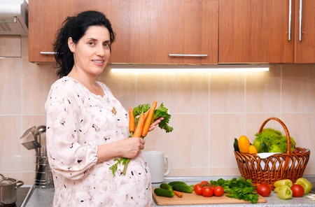 expect: pregnant woman in kitchen interior with fresh fruits and vegetables, healthy food concept
