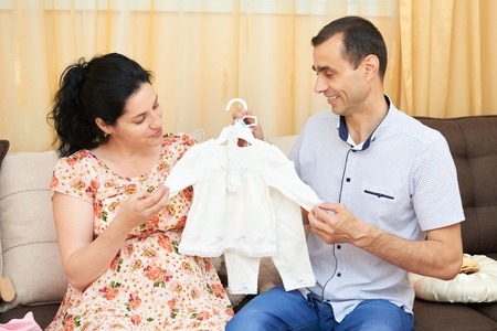 expect: parents choose clothes for the newborn baby. pregnant woman and man. happy couple sitting on the couch at home