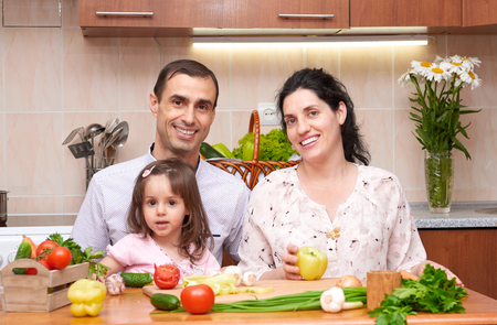 expect: happy family with child in home kitchen interior with fresh fruits and vegetables, pregnant woman, healthy food concept