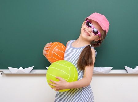 Schoolgirl with paper boat and balloon play near a blackboard, empty space, education concept Stock Photo