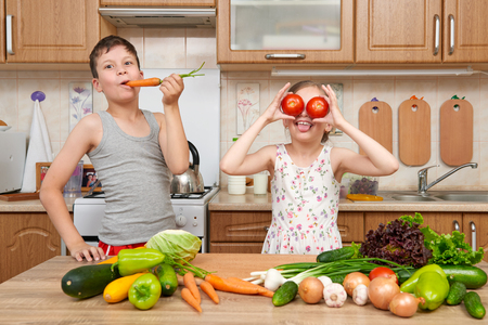 see through: Child girl and boy having fun with tomatoes and carrot, look through like binoculars. Home kitchen interior with fruits and vegetables. Healthy food concept