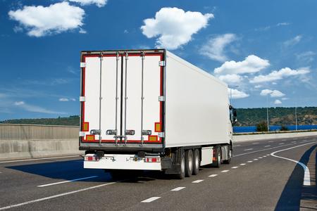 Vrachtwagens met lading op weg, verschepend en vervoersconcept