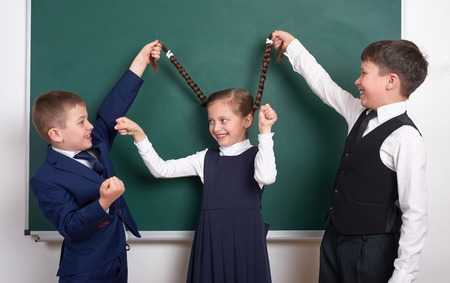 child play and having fun, boys pull the girl braids, near blank school chalkboard background, dressed in classic black suit, group pupil, education concept Stock Photo