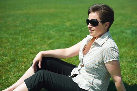 sitt: Woman portrait in summer outdoor, sitt on green grass, happy people, city park Stock Photo