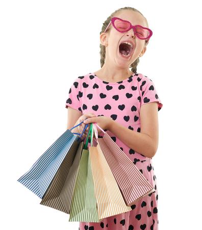 La bambina graziosa sbadiglia con il sacchetto della spesa, ritratto dello studio, vestito nel rosa con le forme del cuore, fondo bianco Archivio Fotografico - 85807106