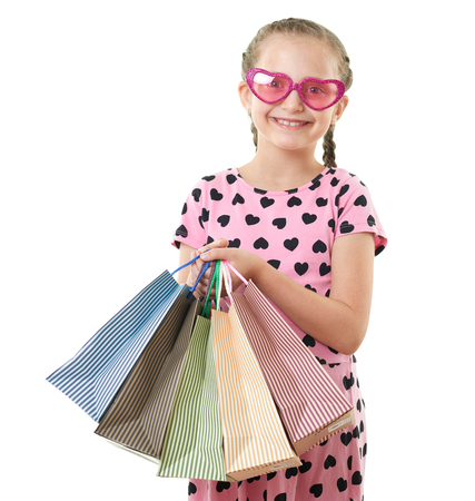 pretty little girl with shopping bag, studio portrait, dressed in pink with heart shapes, white background Stock Photo