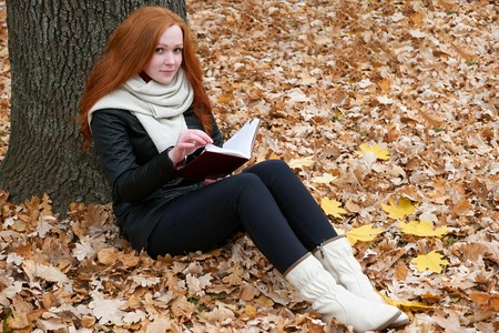 young woman sit near tree in autumn park and read book, yellow leaves