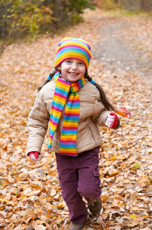 child girl runs on a footpath in autumn forest through fallen leaves background