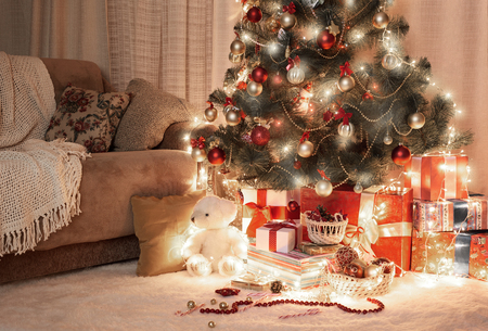 Room in dark with illuminated christmas tree, decoration and gifts, home interior at night