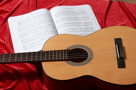 acoustic guitar and music notes on red fabric, close view of objects