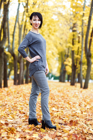 young woman posing in autumn park with yellow trees, fall season