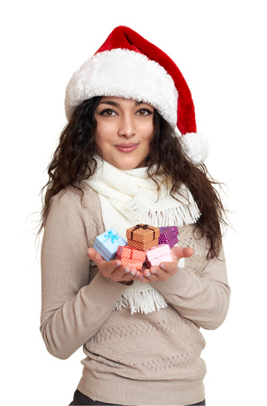 Beautiful girl portrait dressed in santa hat with handful of little gift boxes. White isolated background. New year eve and winter holiday concept.