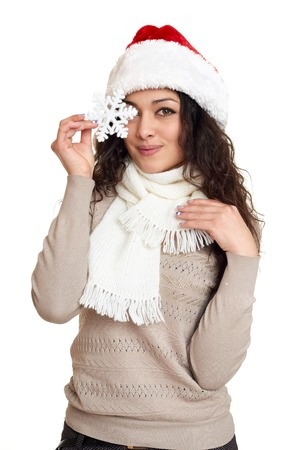 Beautiful girl portrait dressed in santa hat show big snowflake toy. White isolated background. New year eve and winter holiday concept. Standard-Bild