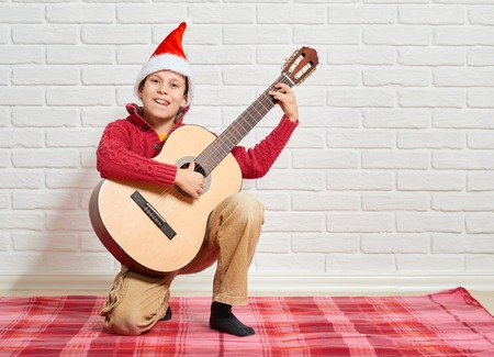 boy playing music on guitar, dressed in a red woolen sweater and santa hat, sitting on a red checkered blanket, white brick wall on background