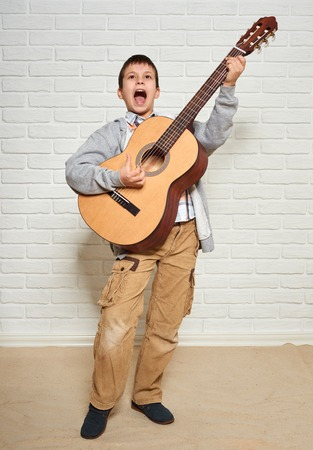 boy playing music on guitar, standing at full height, white brick wall background